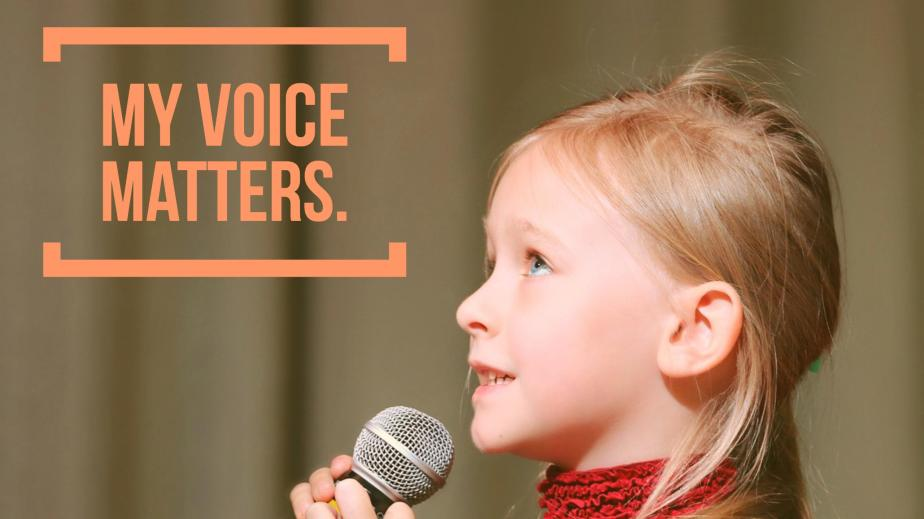 """A close-up of a young girl's face. She holds a microphone to her lips as she looks up, about to speak/sing. Caption reads """"My Voice Matters."""""""