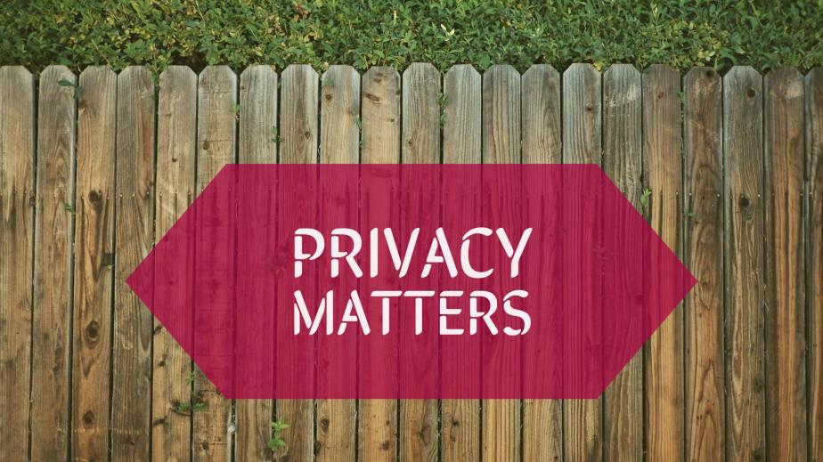 """A wooden fence with a small amount of grass beyond it. A caption in a red box over the fence reads """"Privacy Matters."""""""