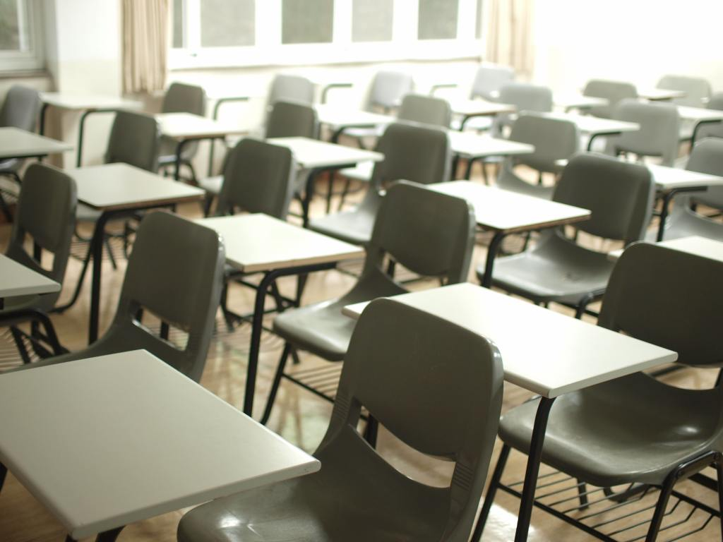 A washed-out photograph of a college classroom filled with empty desks and chairs.